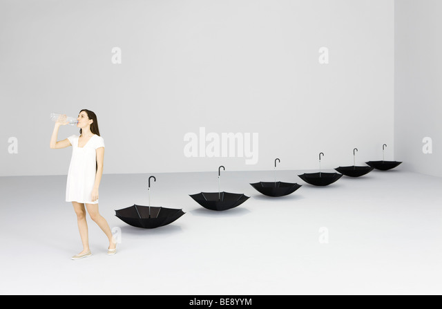 Woman drinking water from bottle, upside down umbrellas lined up behind her - Stock Image