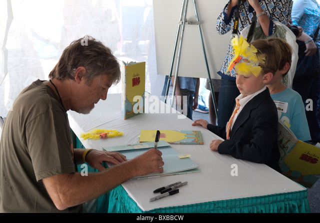 Children's book author/illustrator Keith Graves signs a copy of his book for a young fan at the Texas Book Festival - Stock Image