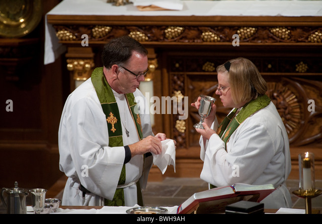 Anglo male presiding minister and Anglo female assisting minister share communion before congregational communion - Stock Image