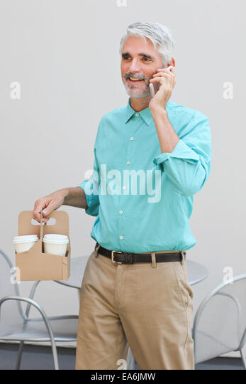 Businessman holding container with coffee cups and talking on mobile phone - Stock Image