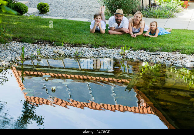 Family with two children takes a break by the pond, Munich, Bavaria, Germany - Stock Image