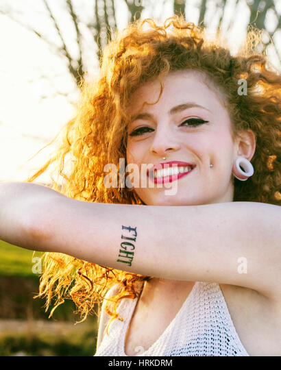 Young alternative redhead woman with piercings and tattooes enjoying the sunset at summer - Stock Image