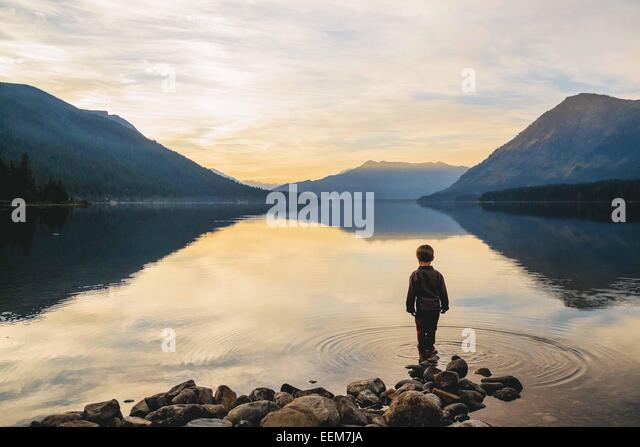 Boy (4-5) standing at water's edge looking at view - Stock-Bilder