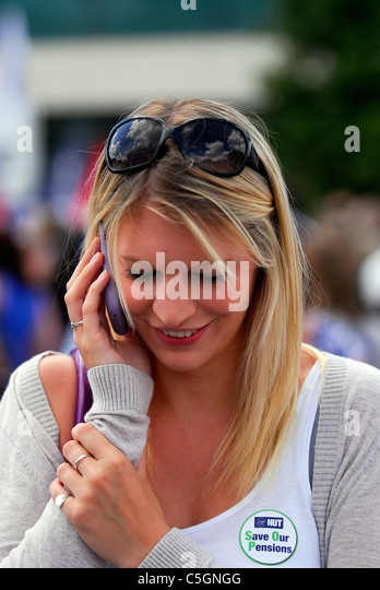 Female speaking on mobile phone whilst attending public sector strike day against spending cuts, Southampton - Stock Image