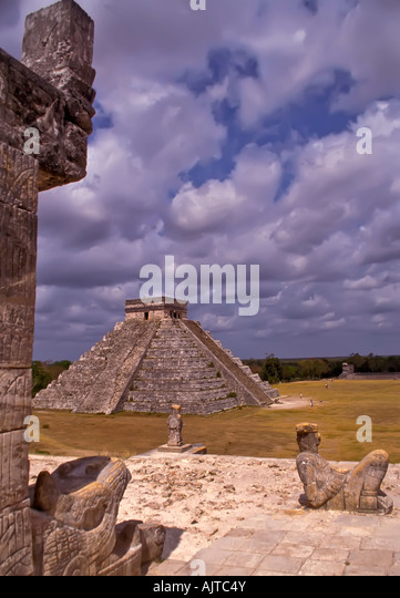 Chichen Itza Mexico pyramid the castle el castillo seen from temple of the warriors with serpent head in foreground - Stock Image