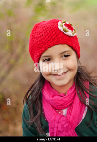 Girl (4-5) wearing a red knit hat smiling outdoors - Stock Image