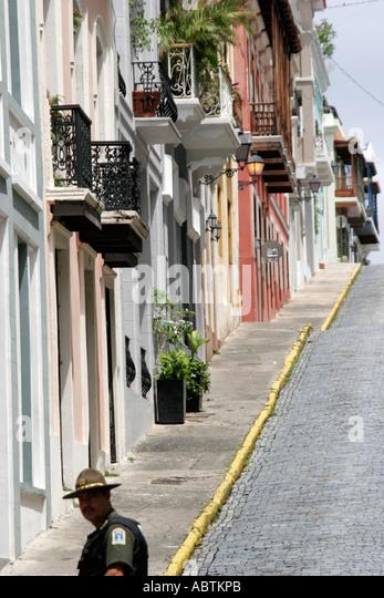 Puerto Rico Old San Juan Calle de la Cruz architecture steep hill Hispanic policeman adoquine cobblestone - Stock Image
