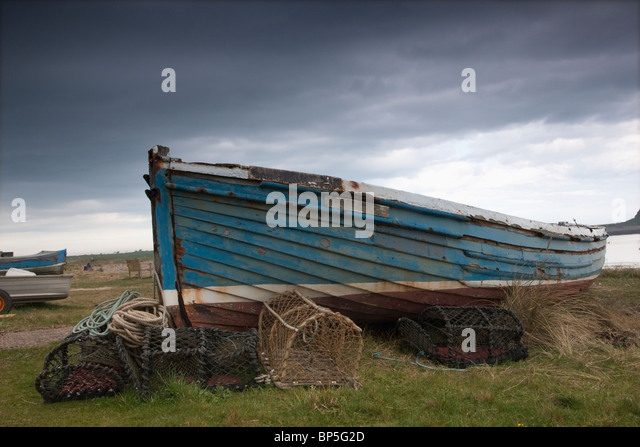 Lindisfarne, Northumberland, England; A Boat And Fishing Traps On The Shore - Stock Image