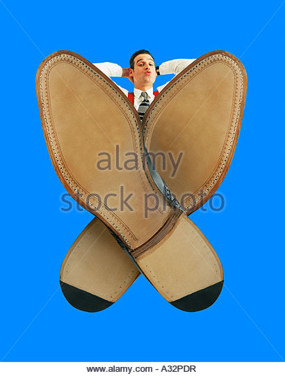 Relaxed looking man with his feet up on the desk, crossed over. Extreme wide-angle effect. - Stock Image