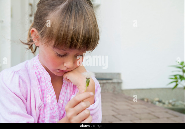 Girl holding dandelion clock looking sad - Stock Image