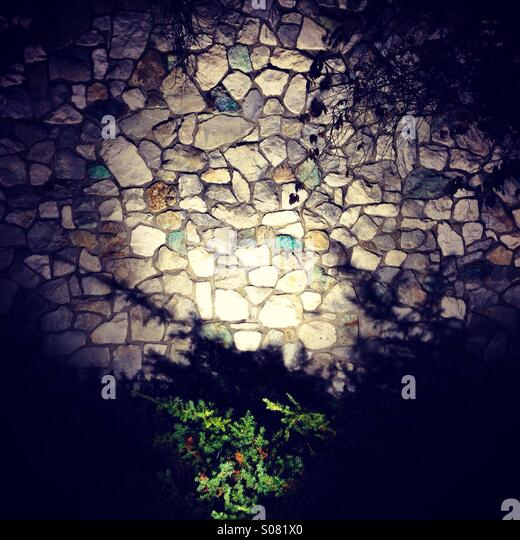 Stone wall with flood light at night - Stock Image