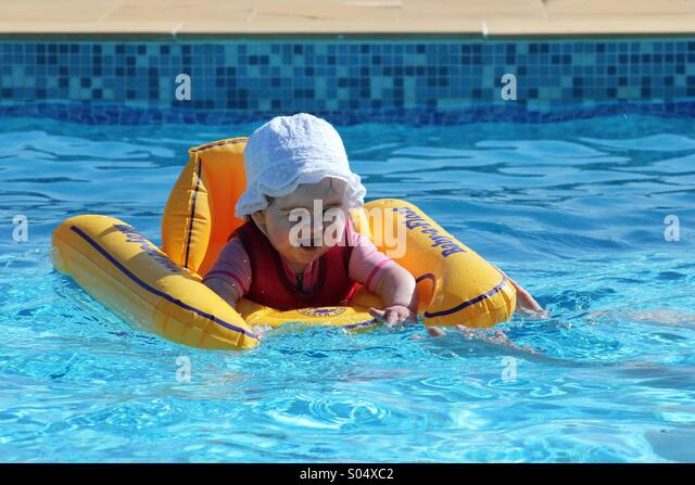 Child playing in swimming pool - Stock Image