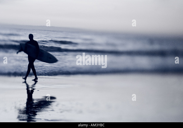 A lone surfer leaves the beach after a day of surfing in Santa Barbara CA - Stock Image