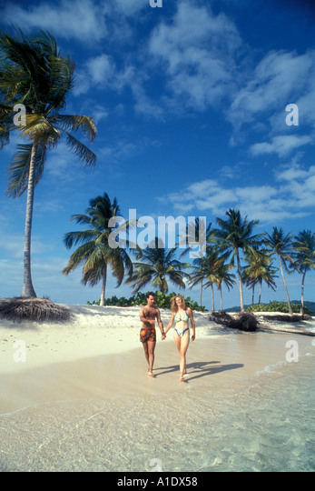 Caribbean Tropics Couple Walking Beach - Stock Image