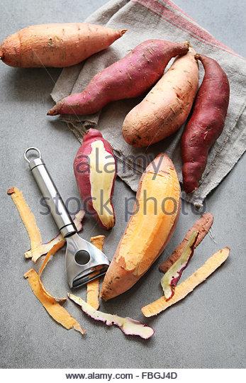 Orange and red japanese  sweet potatoes on grey background - Stock Image