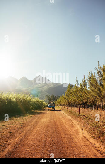 Outdoor image of distant car approaching on a rural dirt road on a sunny day. Automobile driving through the country - Stock Image