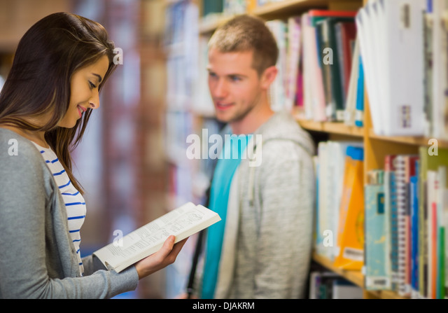 Young couple by bookshelves in the library - Stock Image