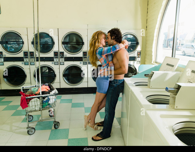 A pretty woman hugs a bared body young man in San Diego coin laundromat. - Stock Image