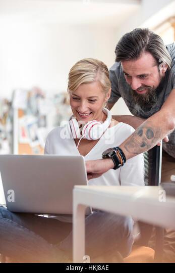 Smiling design professionals working at laptop in office - Stock-Bilder