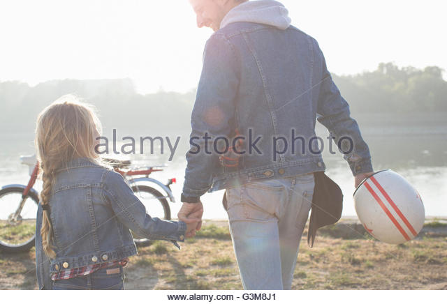 Father and daughter, holding hands, beside lake, rear view - Stock Image
