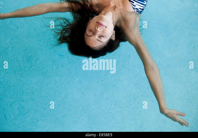 Woman floating in pool with eyes closed - Stock Image