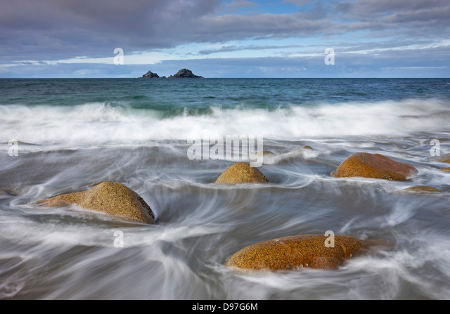 Waves swirl around rocks on Porth Nanven beach, Cornwall, England. - Stock Image