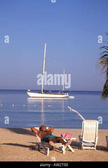Jamaica Negril Man Asleep in Beach Chair Sailboat Behind Him - Stock Image