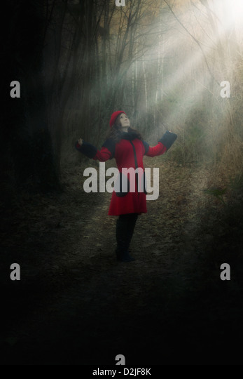 a woman in a red coat is standing in a dark forest in a spot of sunlight - Stock Image