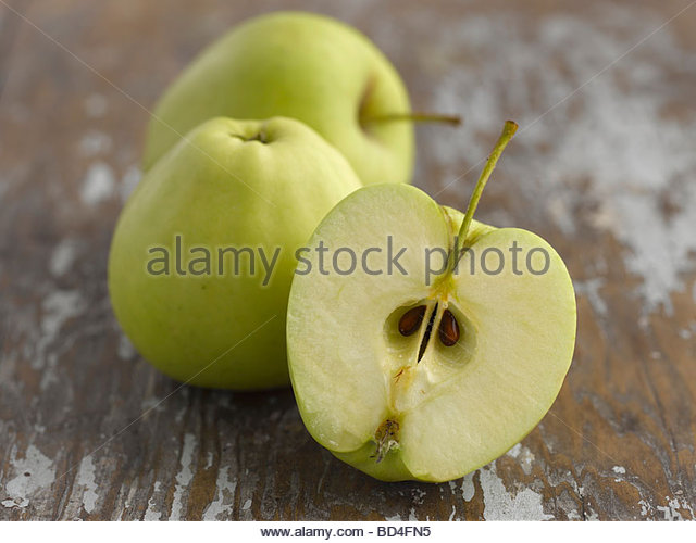 Whole apples and half an apple (Golden Delicious) - Stock Image