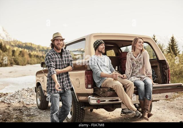 Three people sitting on back of pickup truck smiling - Stock Image