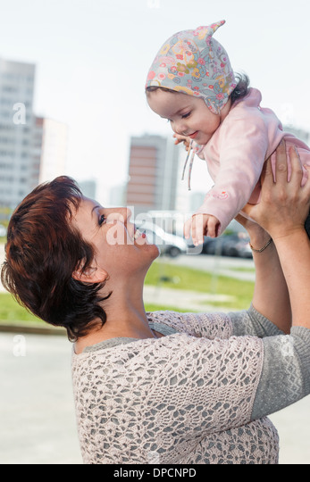 Portrait of a happy mother at city with the child on hands. - Stock Image