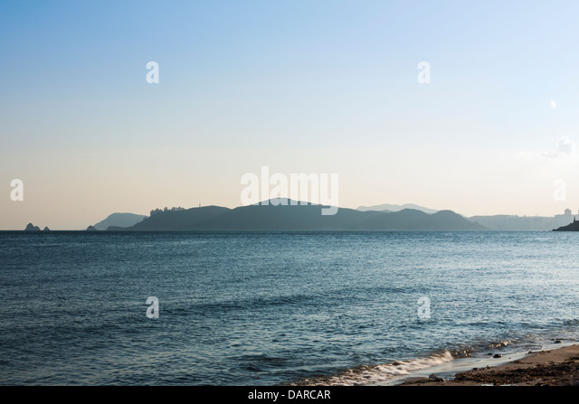 View from Haeundae Beach in Busan towards Nam-gu in Southern Busan and Oryukdo islands during sunset on a windy - Stock Image