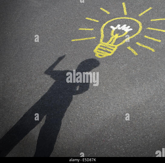 Childhood imagination and child creativity concept as the shadow of an inspired boy with a lightbulb chalk drawing - Stock Image