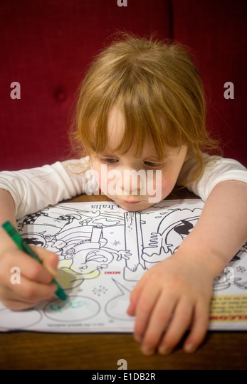 Four year 4 old girl drawing and coloring in with crayons - Stock-Bilder