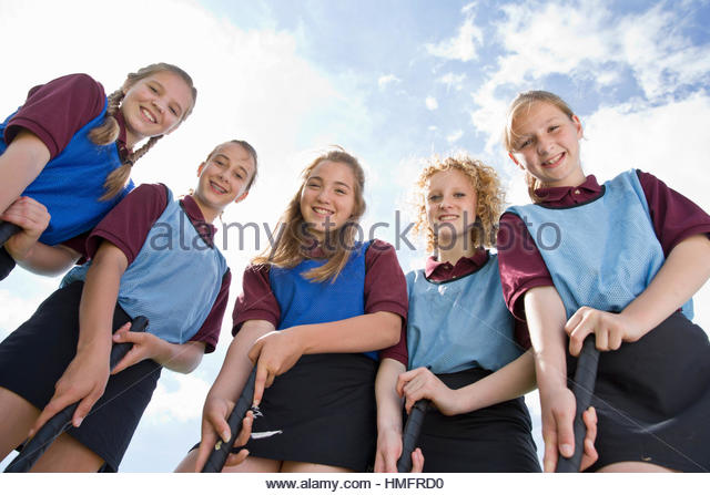 Portrait smiling middle schoolgirls playing field hockey in physical education class - Stock-Bilder
