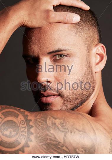 Tattooed mid adult man looking at camera. - Stock Image