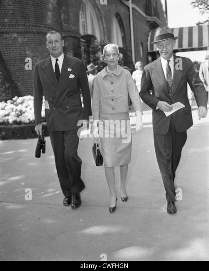 Winston F.C. Guest and his wife, C.Z. Guest, with an unidentified man walking at the Saratoga Race Course, Saratoga, - Stock Image
