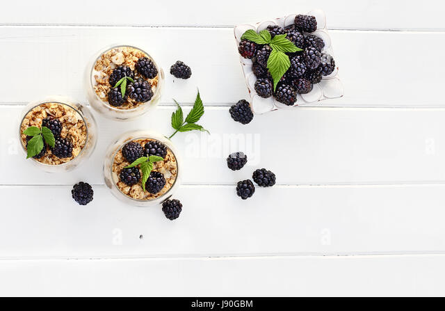 Blackberry parfaits made with Greek yogurt, granola and fresh blackberries shot from overhead over white wood table. - Stock Image