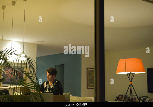 Man using laptop in living room, viewed through window - Stock-Bilder