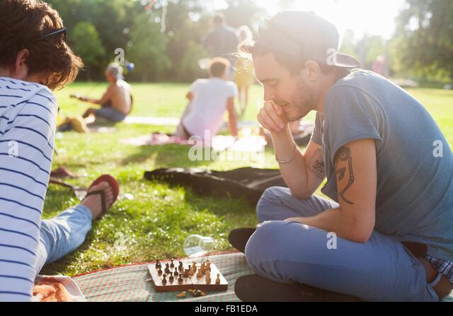 Young adults playing board game at sunset party in park - Stock Image