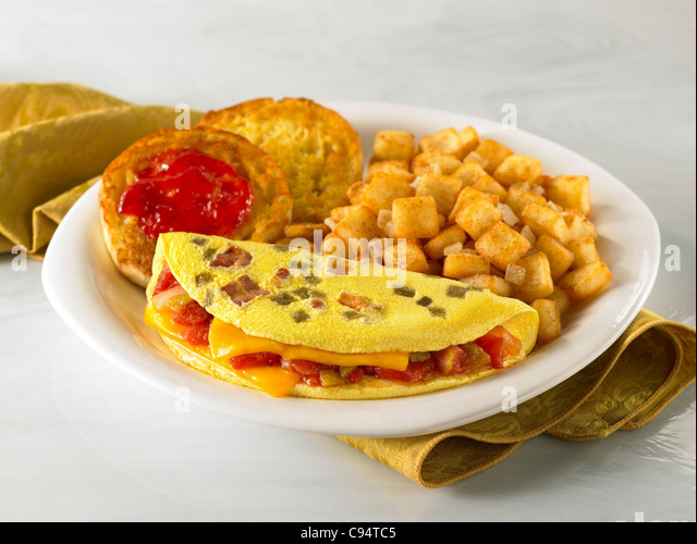 A bacon, vegetable and cheese omelet served with potato and english muffin with jelly - Stock Image