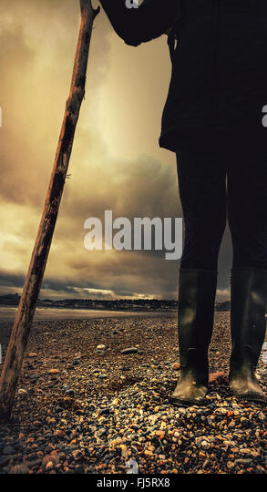 traveling character walking on the pebble beach holding wooden stick - Stock Image