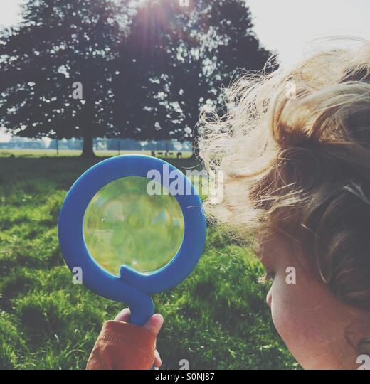 Boy looking for deer with a magnifying glass - Stock-Bilder