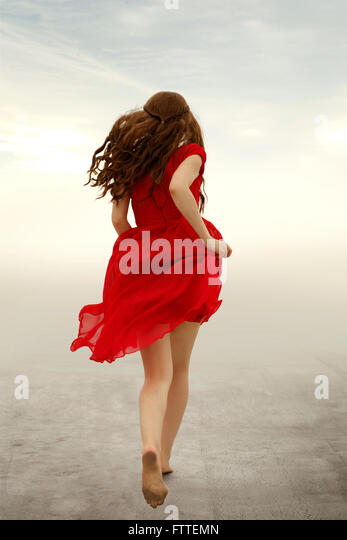 Woman in red dress running away - Stock Image