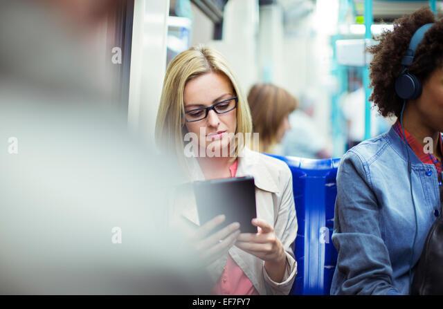 Businesswoman using digital tablet on train - Stock-Bilder