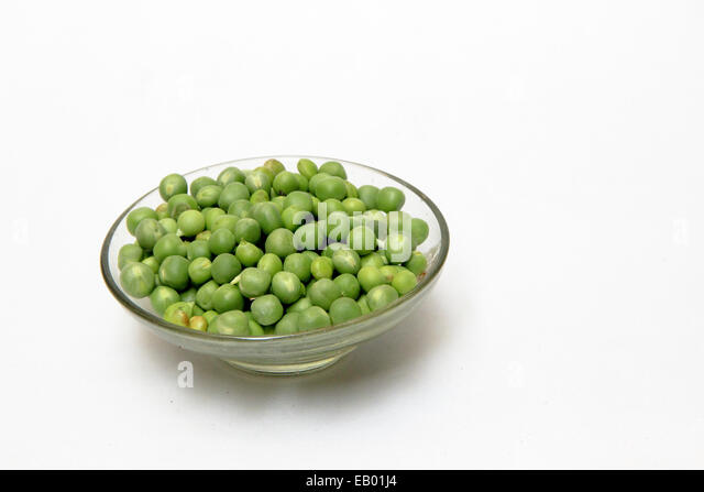 Glass dish containing fresh green peas, isolated on white - Stock Image