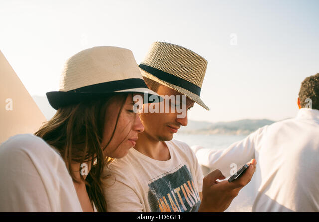 Young Couple With Hat Using Smart Phone At Beach - Stock Image