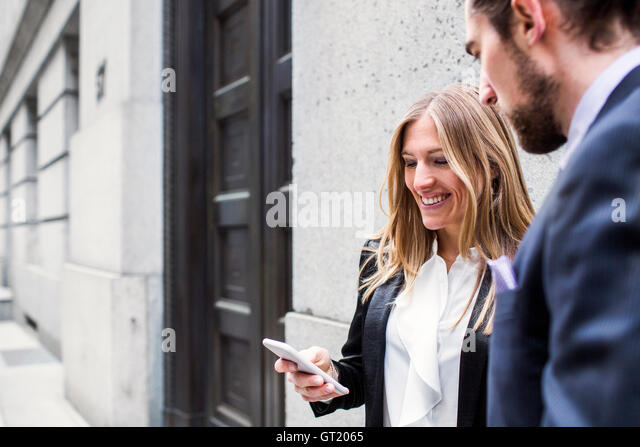 Smiling businesswoman showing smart phone to man while standing against building - Stock-Bilder
