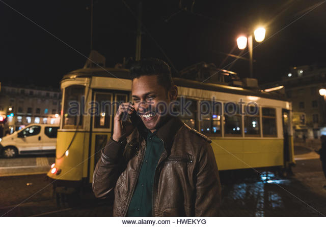 Mid adult man, walking through city at night, using smartphone, Lisbon, Portugal - Stock-Bilder