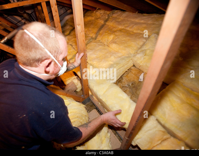 Loft insulation. A worker from Total Insulation Solutions lays insulating material in a loft. - Stock Image